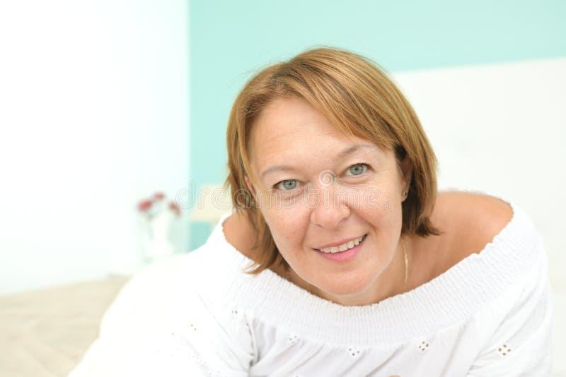 Cara de encontro da mulher feliz para baixo e olhando a câmera na cama do quarto em um ambiente claro que corresponda a um escand imagens de stock
