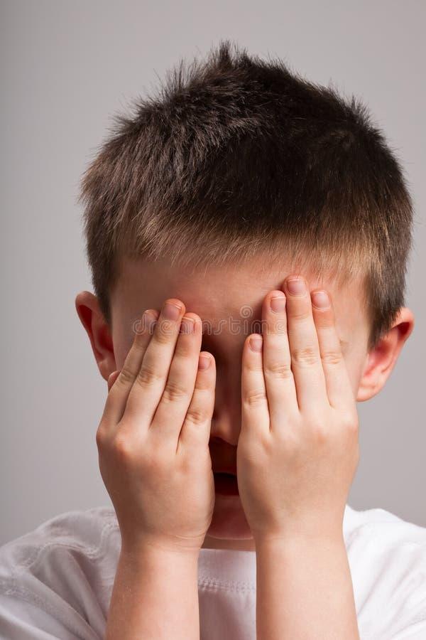 Cara de la cubierta del niño pequeño con las manos imagenes de archivo