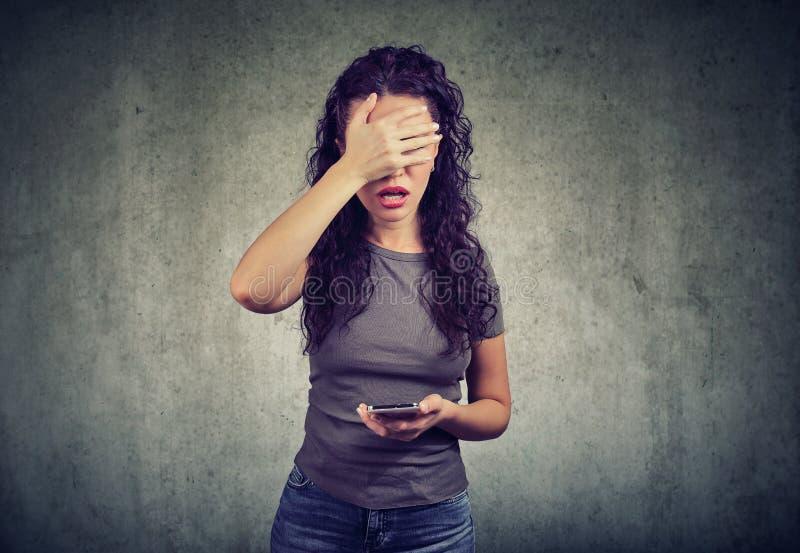 Cara de la cubierta de la mujer en la desesperación que tiene malas noticias en smartphone contra fondo gris foto de archivo libre de regalías