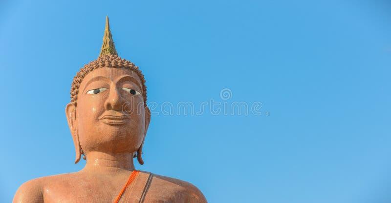 Cara de la estatua de Buda aislada en fondo azul con el spac de la copia fotos de archivo
