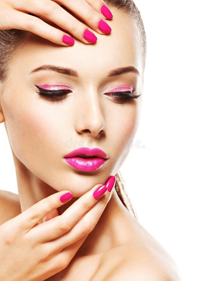 Cara de la mujer de Eautiful con el maquillaje rosado de ojos y de clavos fotografía de archivo