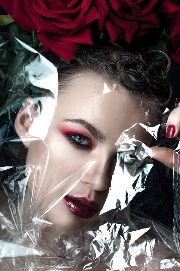 Cara de la mujer del modelo de moda de la belleza Retrato con las flores de la rosa del rojo Labios y clavos rojos Mujer morena h imágenes de archivo libres de regalías