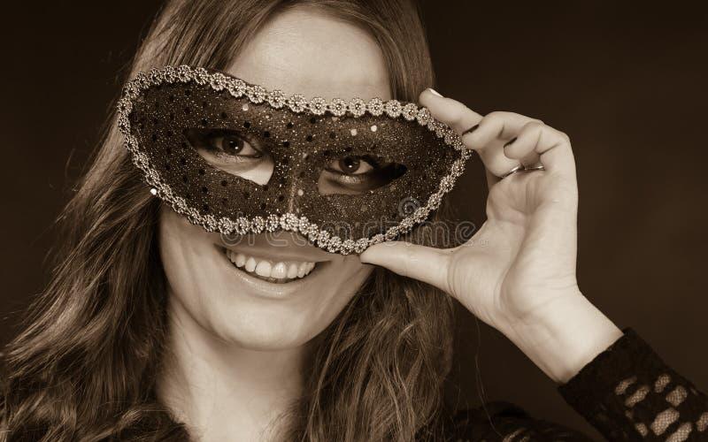 Cara de la mujer del primer con la máscara del carnaval en oscuridad imagen de archivo libre de regalías