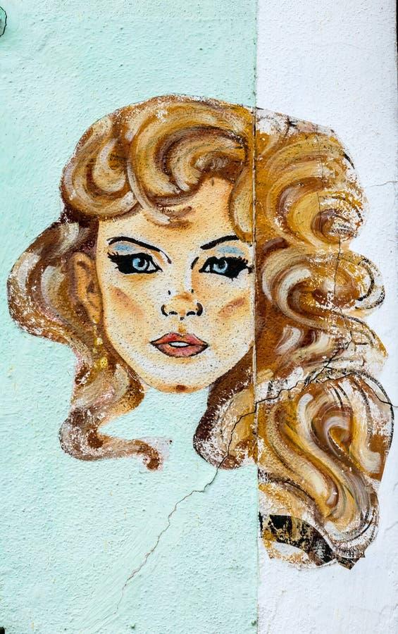 Cara de la mujer en una pared de la casa fotos de archivo