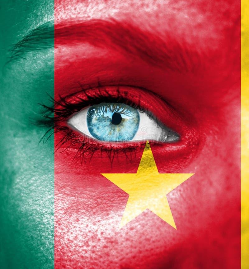 Cara de la mujer pintada con la bandera del Camerún fotos de archivo libres de regalías