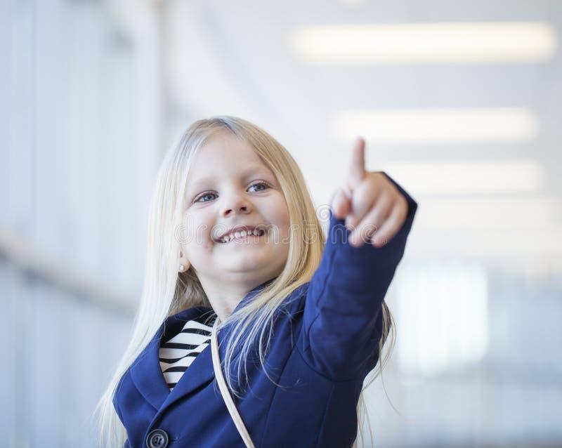 Cara de la niña feliz en chaqueta azul que señala en algo imagenes de archivo