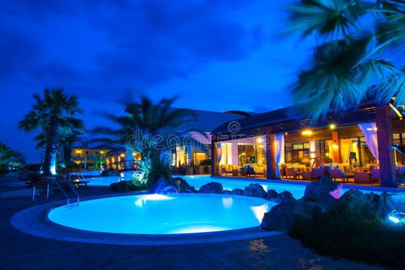 Cara de la piscina de la noche del hotel rico foto de archivo