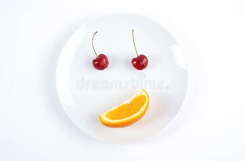 Cara de la sonrisa creada de dos cerezas y naranjas foto de archivo