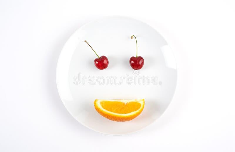 Cara de la sonrisa creada de dos cerezas y naranjas fotos de archivo