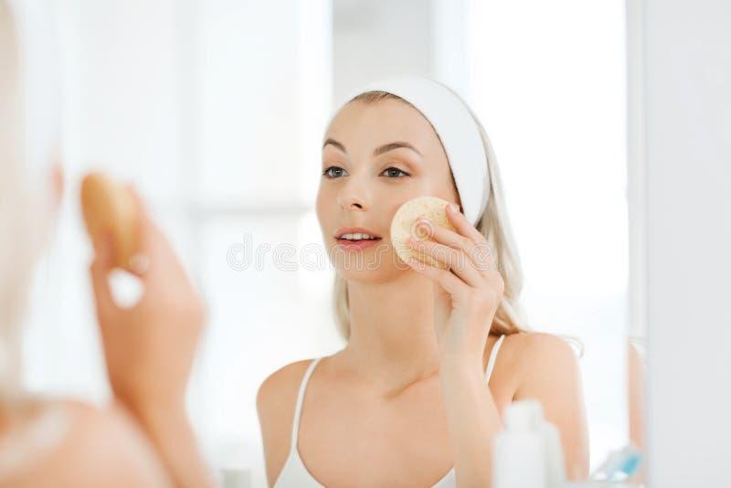 Cara de lavagem da jovem mulher com a esponja no banheiro foto de stock royalty free