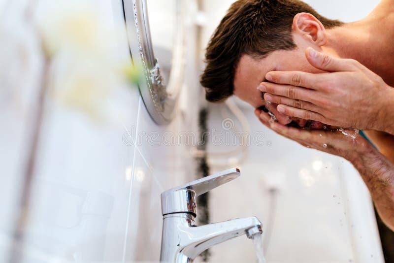Cara de lavagem do homem na manhã imagem de stock
