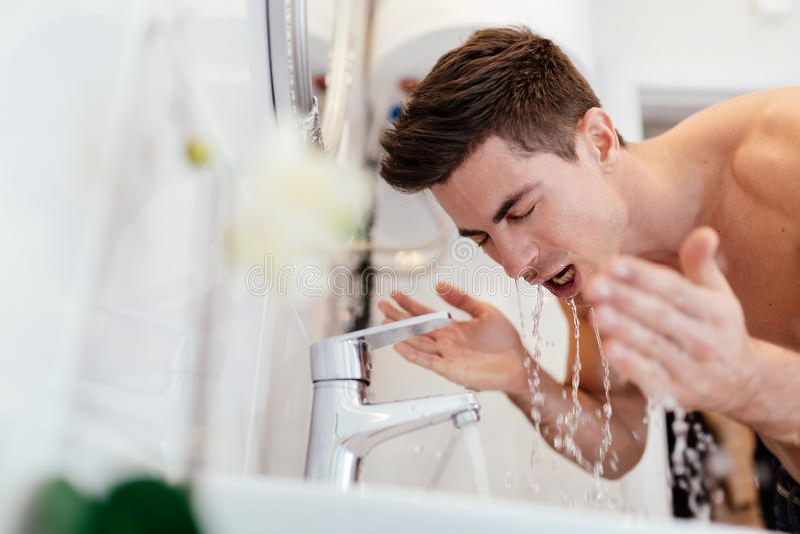 Cara de lavagem do homem na manhã imagens de stock