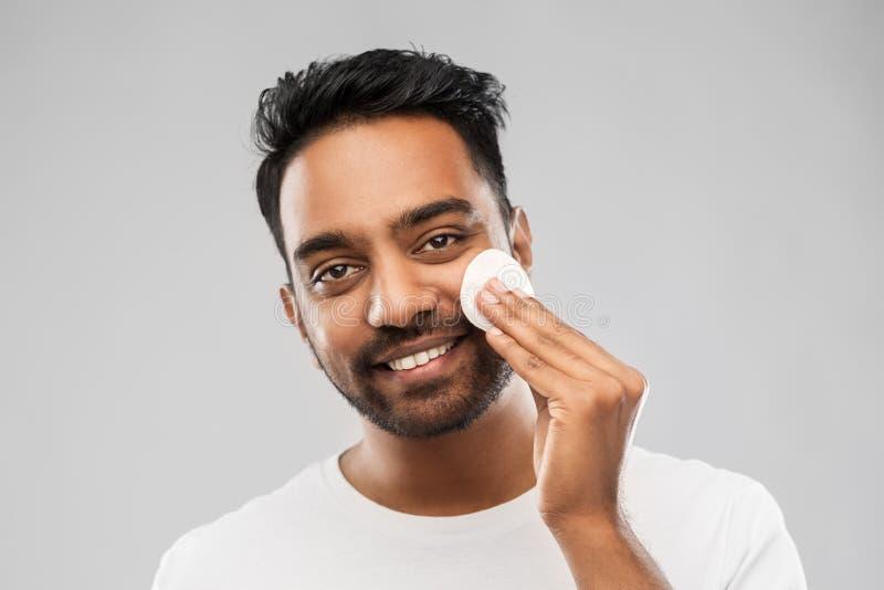 Cara de limpeza de sorriso do homem indiano com almofada de algodão fotos de stock royalty free