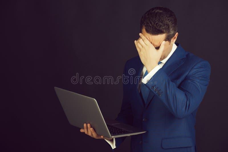 Cara de ocultación del hombre o del encargado con la mano en traje azul imagen de archivo libre de regalías