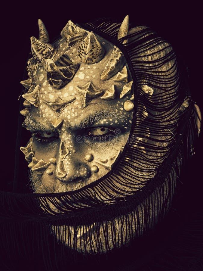 Cara de ocultaci?n del demonio con la bufanda aislada en negro fotografía de archivo