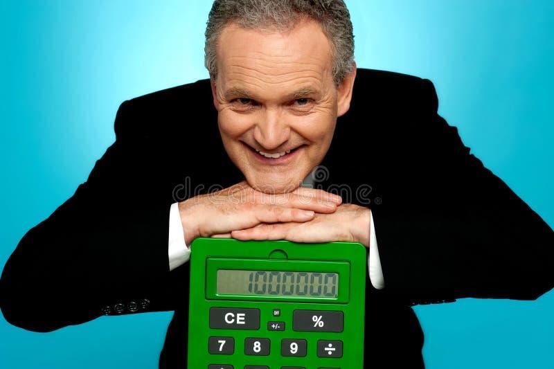 Cara de reclinación masculina corporativa envejecida en la calculadora grande imágenes de archivo libres de regalías