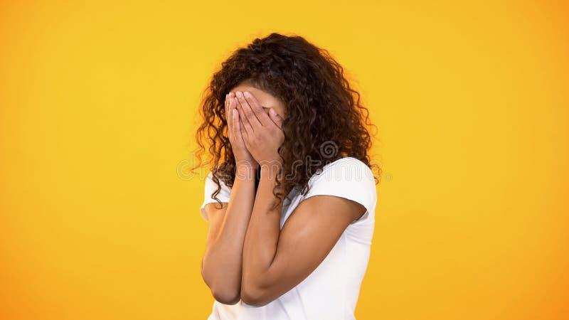 Cara de recubrimiento femenina asustada por las manos en el fondo brillante, persona asustada imagen de archivo
