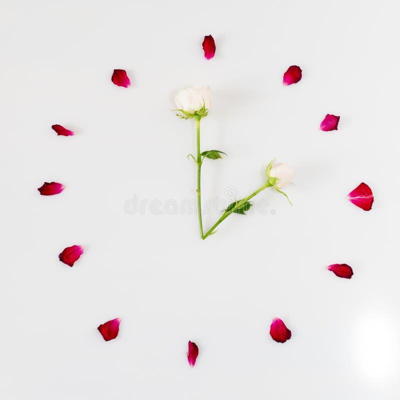 Cara de reloj hecha de pétalos color de rosa Mida el tiempo del concepto fotos de archivo libres de regalías