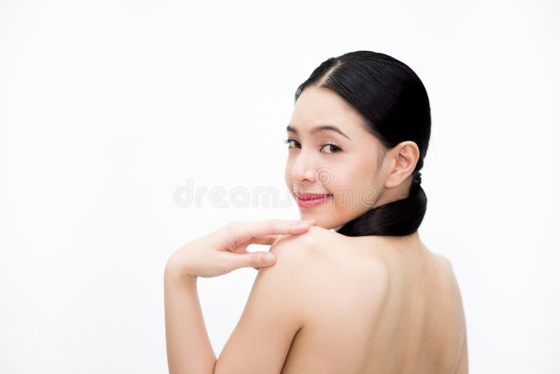 Cara de sorriso de giro da mulher asiática nova da beleza e mostrar a parte traseira desencapada isolada sobre o fundo branco imagens de stock