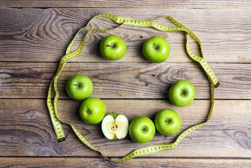 Cara de sorriso de maçãs verdes e da fita amarela do centímetro em w velho imagens de stock royalty free