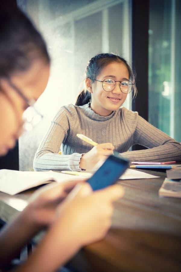 Cara de sorriso Toothy da menina asiática que faz o trabalho da casa da escola na sala de visitas da casa imagem de stock