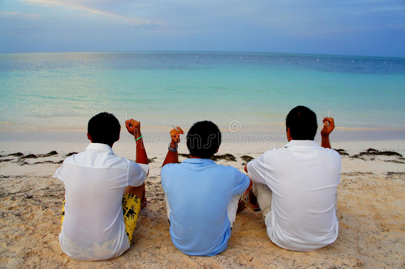 Cara de tres hombres al océano que se relaja con el cigarret en la playa en Playa de Bavaro, cana de Punta, República Dominicana fotos de archivo