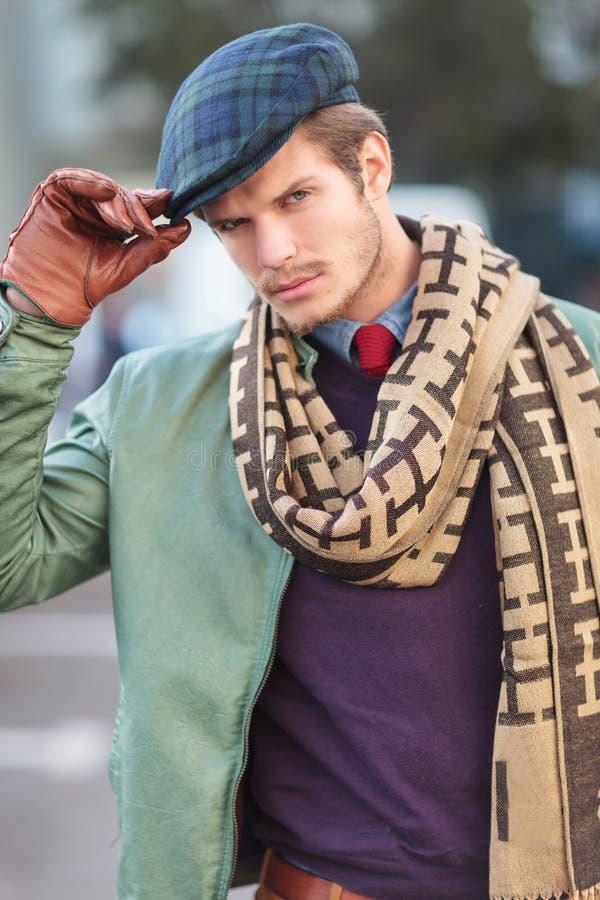 Cara de um homem novo elegante que guarda seu chapéu foto de stock royalty free
