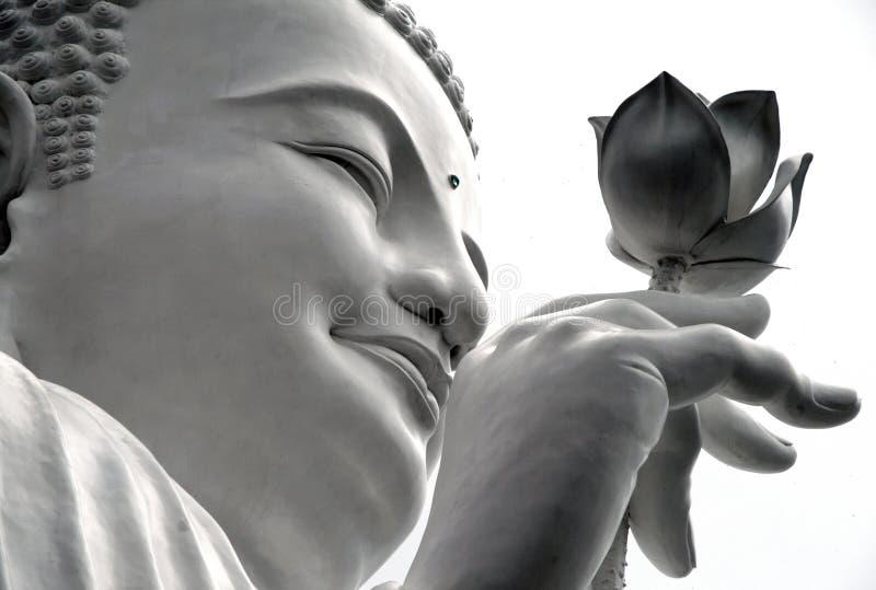 Cara de uma Buda branca com uns lótus em sua mão, Dalat, Vietname imagens de stock royalty free