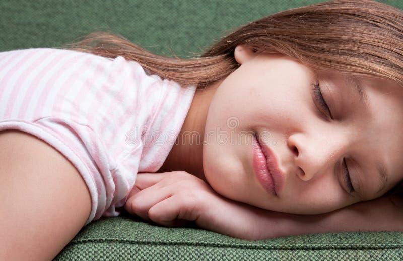 Cara de uma menina doce pequena que dorme em um sofá imagem de stock royalty free