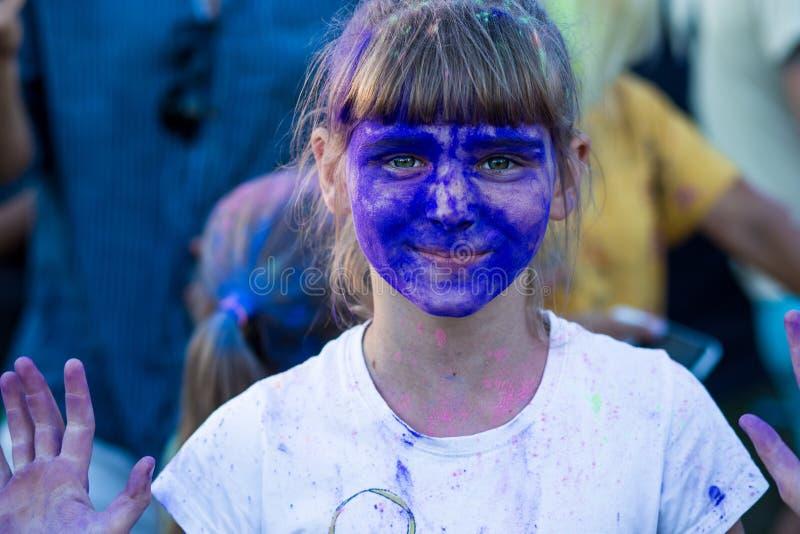A cara de uma menina em pinturas azuis do holi imagens de stock royalty free
