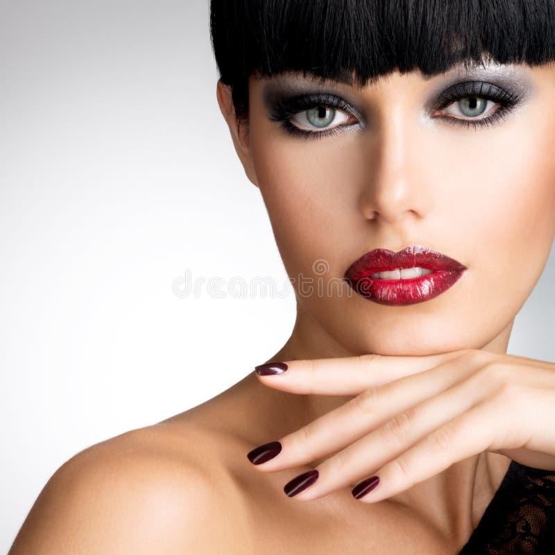 Cara de uma mulher com os pregos escuros bonitos e os bordos vermelhos 'sexy' imagens de stock