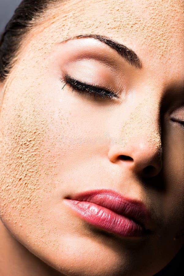 Cara de uma mulher com pó cosmético na pele foto de stock royalty free