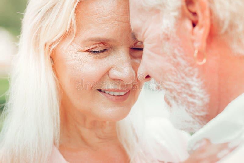 Cara de uma mulher envelhecida agradável ao abraçar seu marido fotos de stock royalty free
