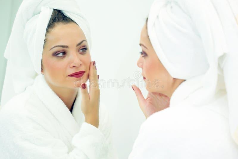 A cara de uma mulher Tratamentos dos termas Cabeça envolvida com uma toalha branca imagem de stock royalty free