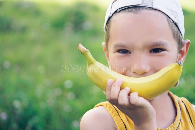 Cara de un muchacho caucásico joven hermoso en casquillo con sonrisa del plátano en fondo de la naturaleza foto de archivo libre de regalías