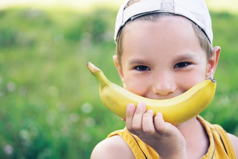 Cara de un muchacho caucásico joven hermoso en casquillo con sonrisa del plátano en fondo de la naturaleza fotografía de archivo libre de regalías