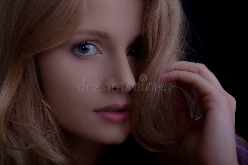 Cara de una muchacha rubia hermosa que mira a la cámara imagen de archivo