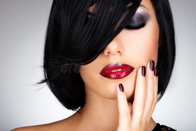 Cara de una mujer con los clavos oscuros hermosos y los labios rojos atractivos imágenes de archivo libres de regalías