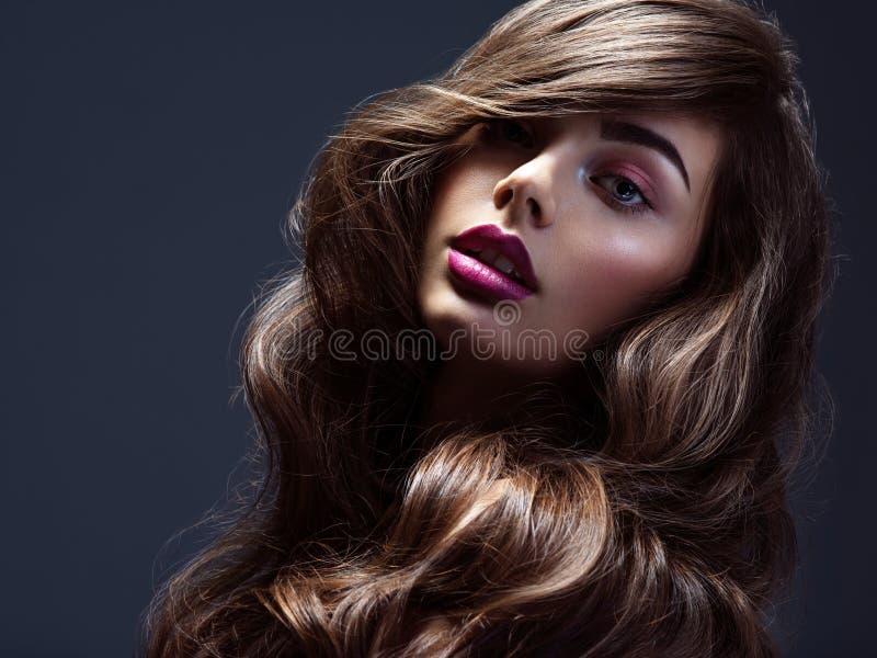 Cara de una mujer hermosa con el pelo largo y rizado marrón Modelo de moda con cabello ondulado Atractiva joven con el pelo rizad foto de archivo