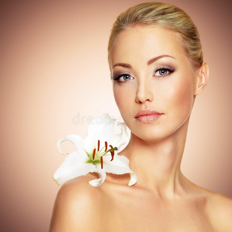 Cara de una mujer hermosa con la flor limpia del piel y blanca fotos de archivo libres de regalías