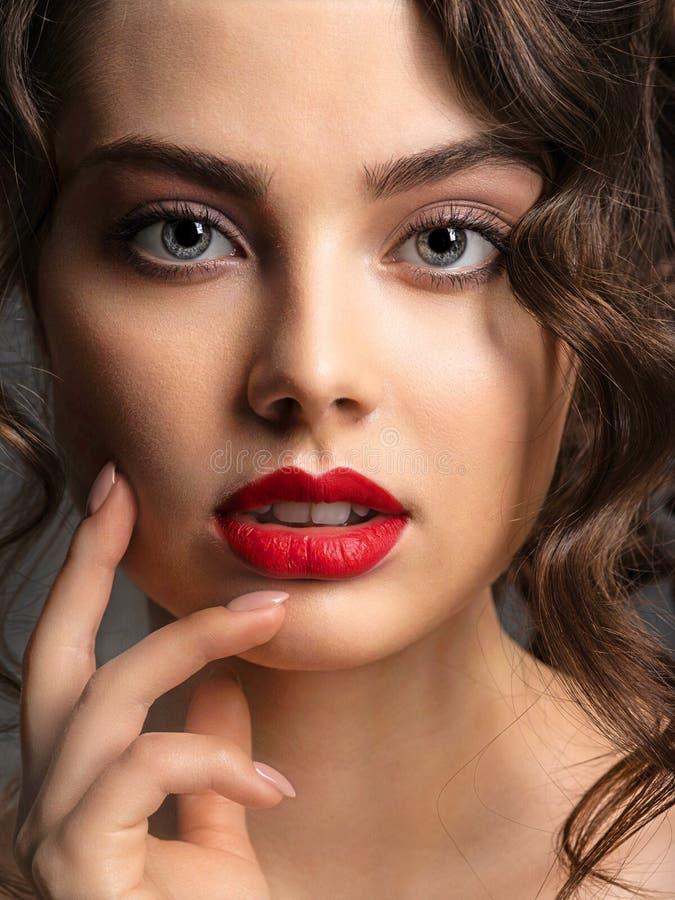 Cara de una mujer hermosa con un maquillaje ahumado del ojo y una barra de labios roja imágenes de archivo libres de regalías