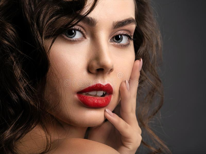 Cara de una mujer hermosa con un maquillaje ahumado del ojo y una barra de labios roja imagenes de archivo