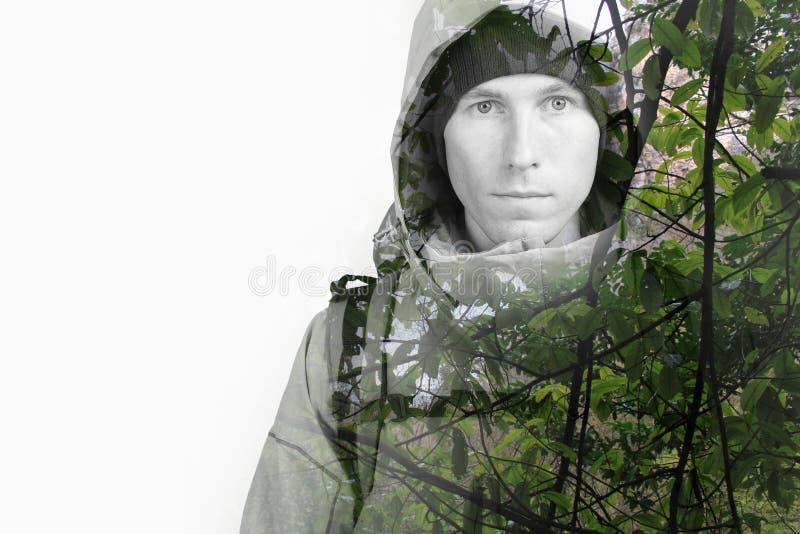 Cara del caminante del hombre joven y de la fotografía salvaje verde del efecto de la exposición doble del bosque imagenes de archivo
