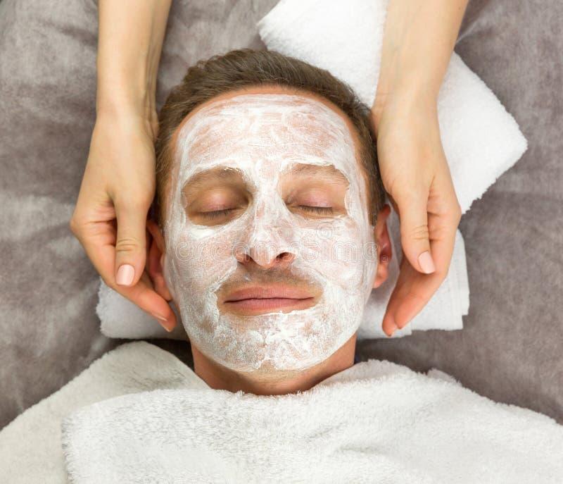 Cara del hombre con la máscara poner crema y de manos del cosmetólogo foto de archivo