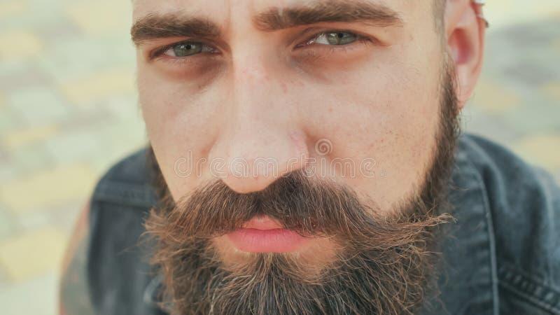 Cara del primer de un hombre de la calle barbudo, brutal y sonriente foto de archivo