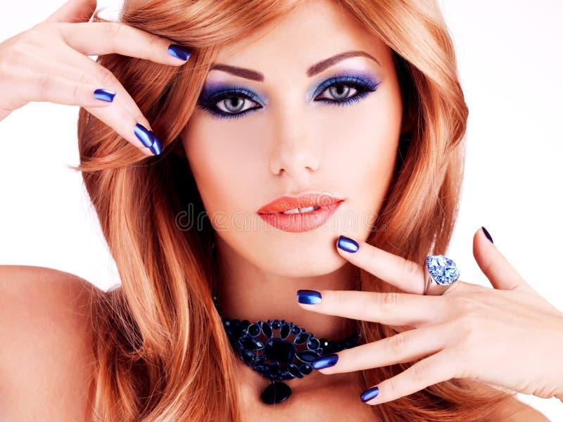 Cara del primer de una mujer hermosa sensual con los clavos azules foto de archivo libre de regalías