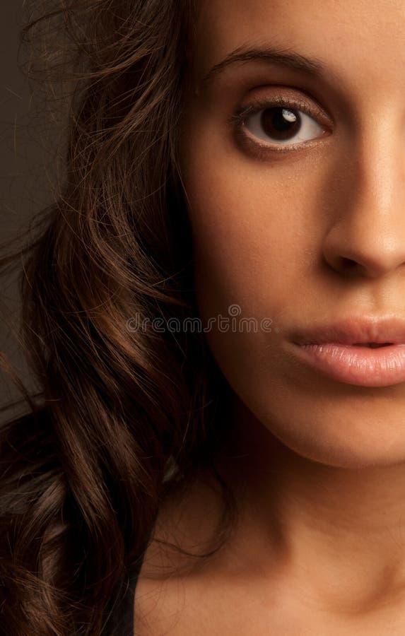 Cara del retrato del primer de la mujer joven media en obscuridad fotografía de archivo libre de regalías