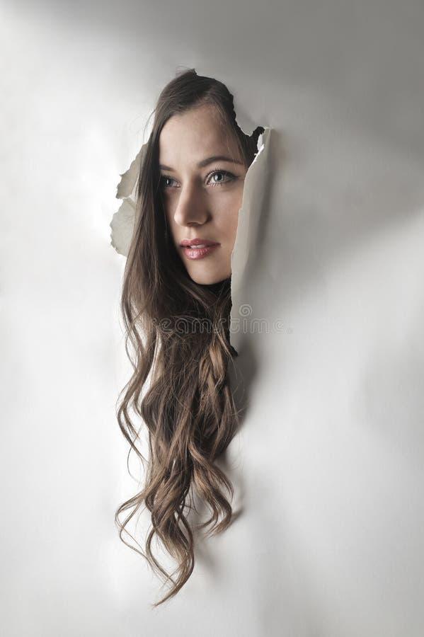 Cara del ` s de la muchacha que viene a través de la pared fotografía de archivo