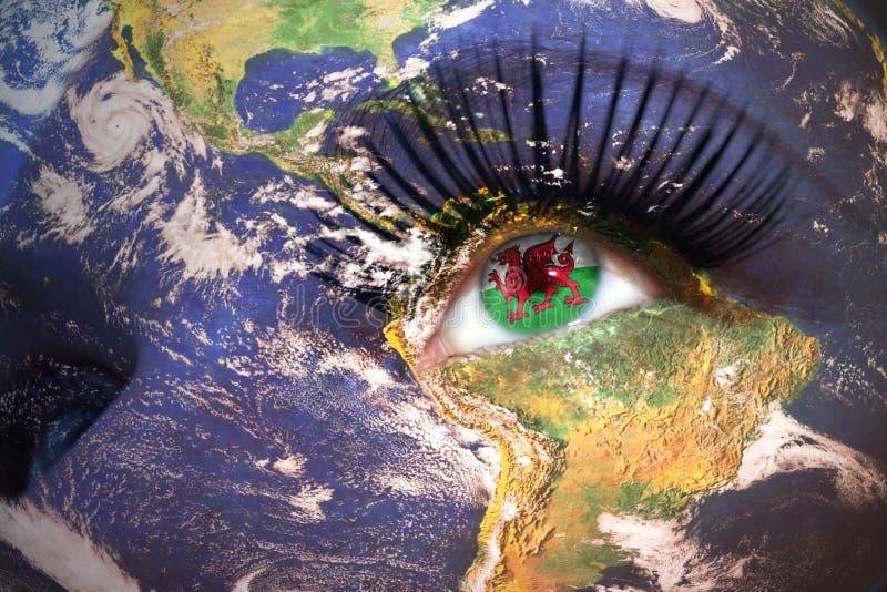 Cara del ` s de la mujer con la bandera de la textura y galés de la tierra del planeta dentro del ojo foto de archivo libre de regalías