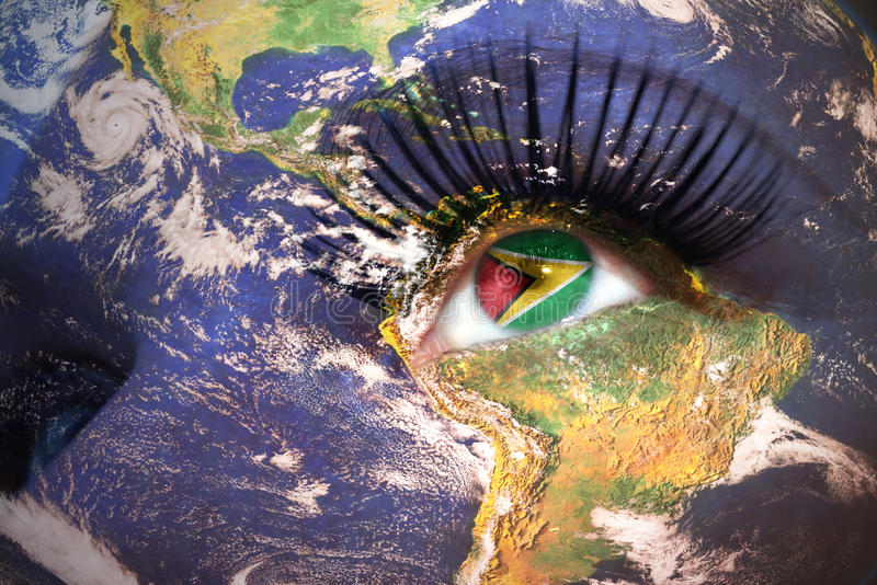Cara del ` s de la mujer con textura de la tierra del planeta y bandera guyanesa dentro del ojo fotografía de archivo